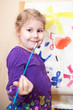 Happy preschool girl painting a picture with paints and brush