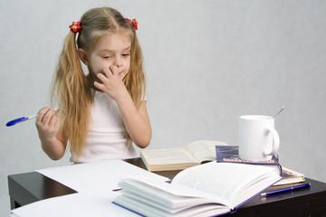 Девочка задумалась и чешет щеку, записывая на листе бумаги