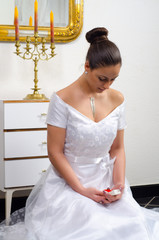 Beautiful bride kneeling and looking at her wedding ring