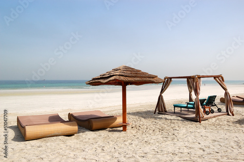 Beach with hut and sunbeds of the luxury hotel, Ajman, UAE