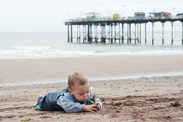 Child on beach with pier, Devon, England