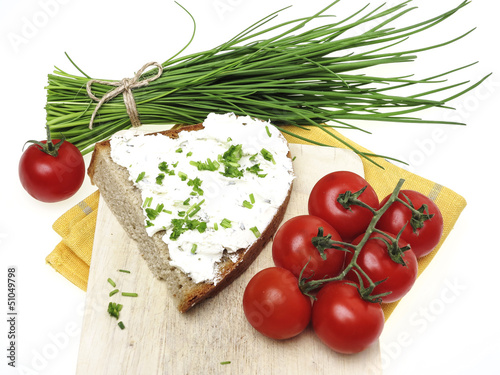 a slice of bread with cheese and chives on white background