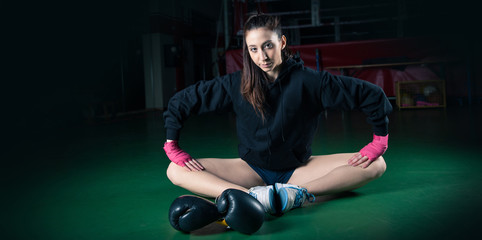 Boxing girl intense portrait against black background.