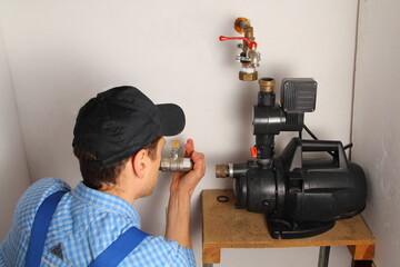 Mann schließt eine Hauswasserpumpe an