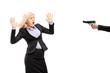 Afraid young businesswoman from a gun