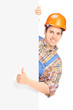 Construction worker posing and giving thumb up on a panel