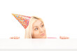 Female with a party hat peeking from under a table