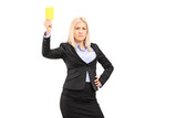 Angry businesswoman holding a yellow card