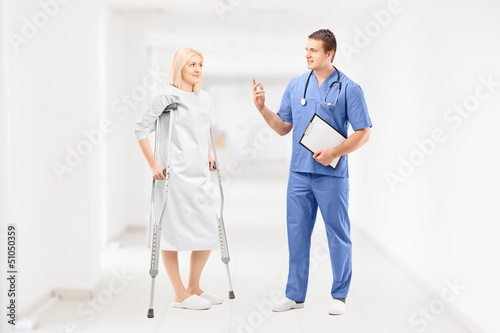 Female patient in gown with crutches and medical doctor during a