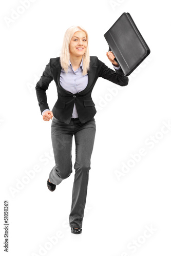 Businesswoman running with a briefcase and looking at camera