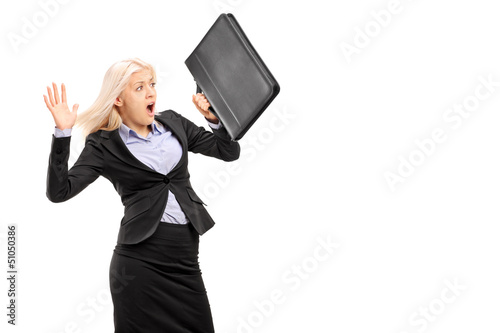 Scared young businesswoman protecting with briefcase and gesturi