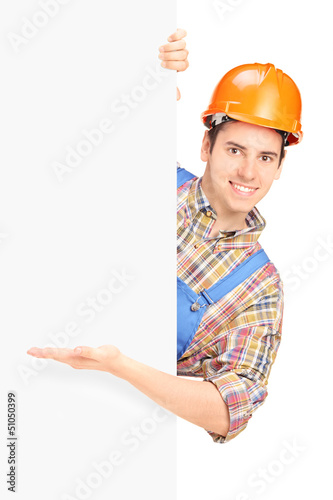 Young construction worker with helmet posing and gesturing on a