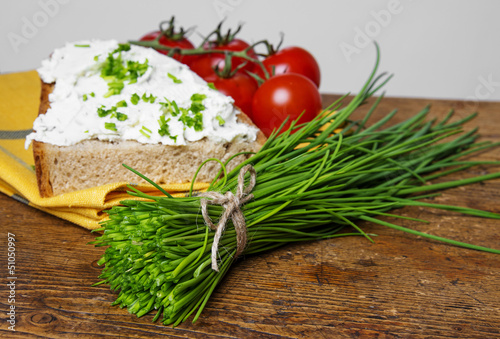 a bunch of fresh chives and a bread with cottage cheese