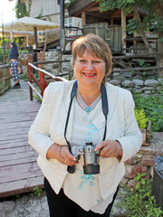 Portrait of smiling middle-aged woman with photo camera