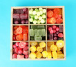 Multicolor candies in wooden box, on color background