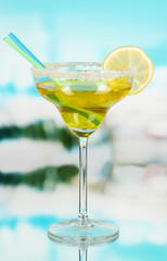 Yellow cocktail in glass on blue natural background
