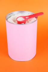 Powdered milk for baby on orange background