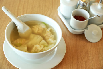 Wonton soup with spoon in a bowl. Traditional asian food