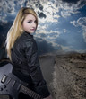 Sexy young blonde dressed in black leather with electric guitar