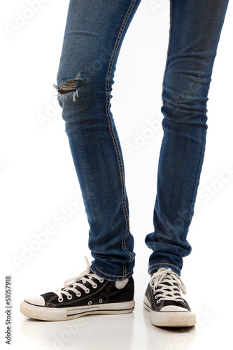 Legs with jeans and retro black sneakers on a white background