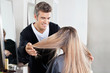 Hairstylist Examining Client's Hair At Salon