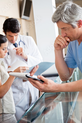 Doctor Reading Document At Reception