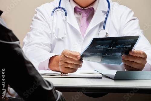 Radiologist At Desk Holding X-ray
