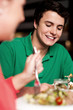 Handsome young guy enjoying meal in restaurant
