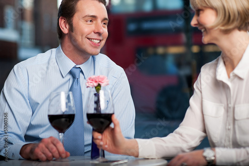 Happy couple drinking red wine at a restaurant