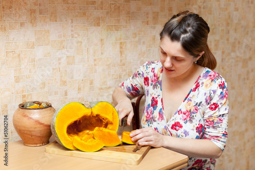 woman  cuts pumpkin