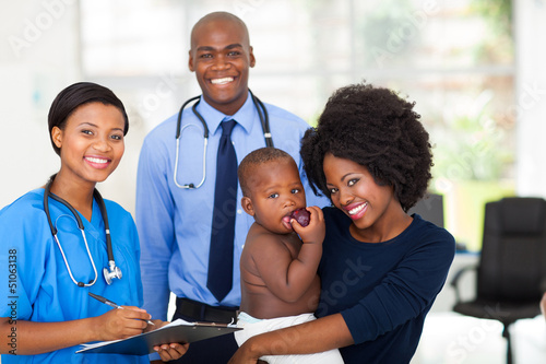 mother holding her baby after checkup with nurse and doctor