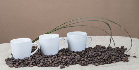Tres tazas de café sobre un montón de granos.