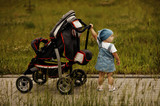 little funny girl with baby carriage