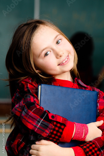 happy little schoolgirl portrait in classroom