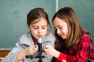 Two schoolgirls have a practice with microscope