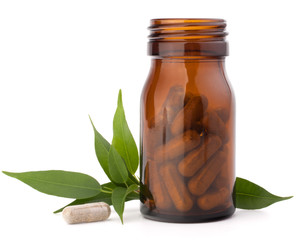 Herbal drug capsules in brown glass bottle. Alternative medicine