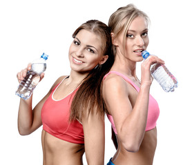 Two beautiful young women drinking water after fitness exercise