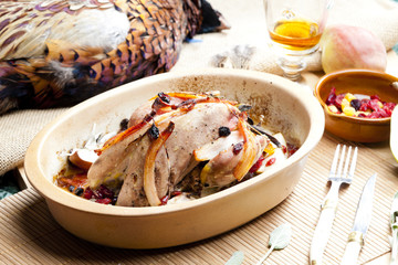 baked pheasant with bacon, pear, raisins on brandy