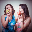 two beautiful girls eating apples