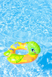 child's green rubber ring in swimming pool