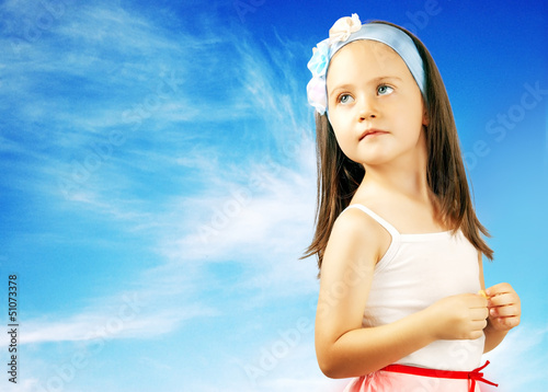 Portrait of a beautiful little girl on the sky