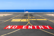no entry sign at the runway of the airport with ocean in backgro