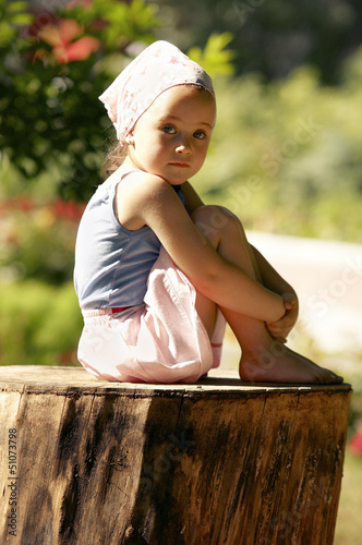 A little sweet girl is sitting on a stump