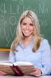 lesende lehrerin lächelt in die kamera