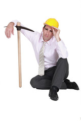 businessman wearing helmet and holding a pick