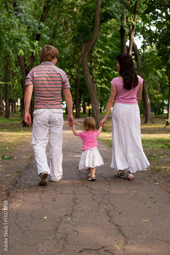 A young family, father, mother and toddler daughter walking in t
