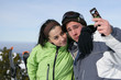 Young couple using a cameraphone on a ski slope