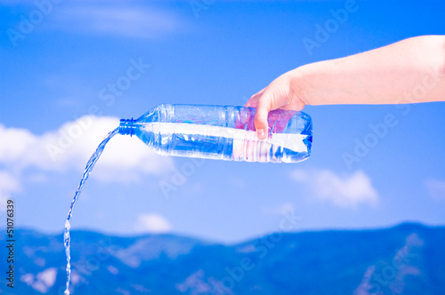 Hand holding bottle with pure water on mountain background
