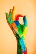 Painted hand with OK sign, colorful fun.