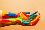 Painted hands, colorful fun. Orange background
